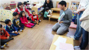 NSLI-Y Student reading a book to a group of kindergartens.