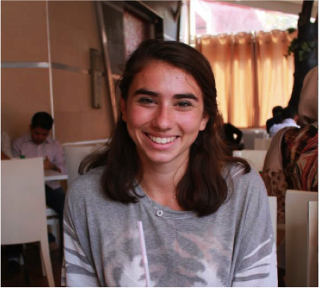 Student sitting in a cafe, smiling, with people sitting at tables behind her