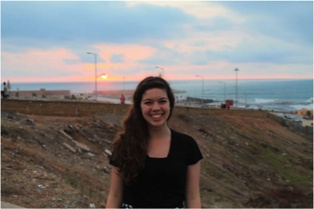 Student smiles in front of view of coastline and sea