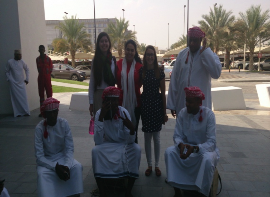 Three students are shown with some performers in traditional Omani dress.