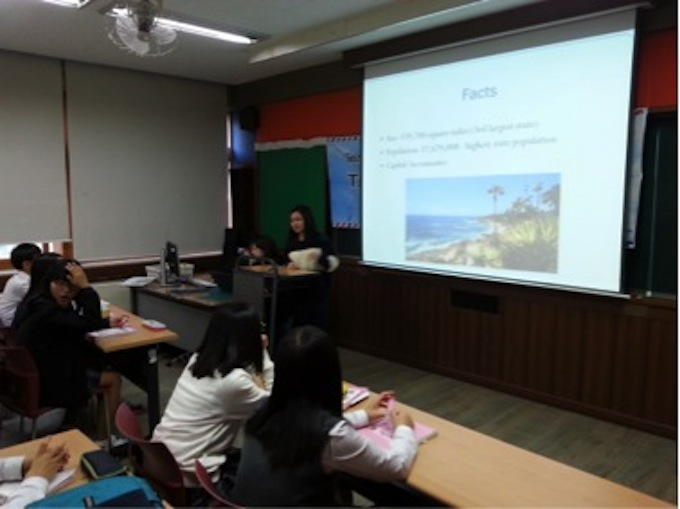 Korean middle schoolers paying attention to a slide show.