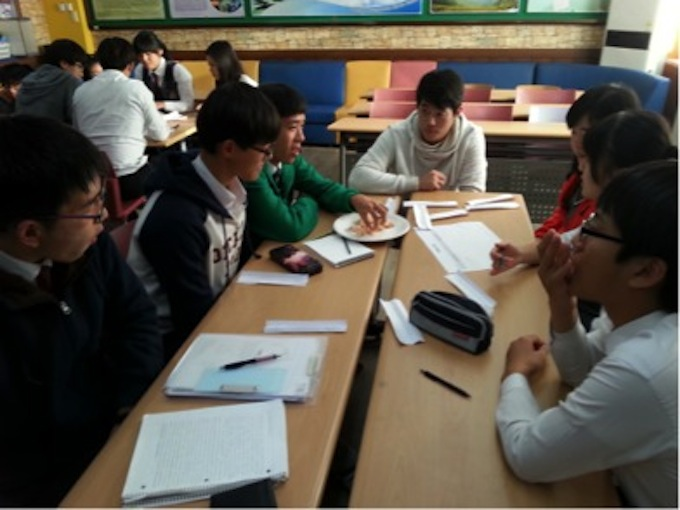 NSLI-Y student sitting down on a table with Korean middle schoolers.