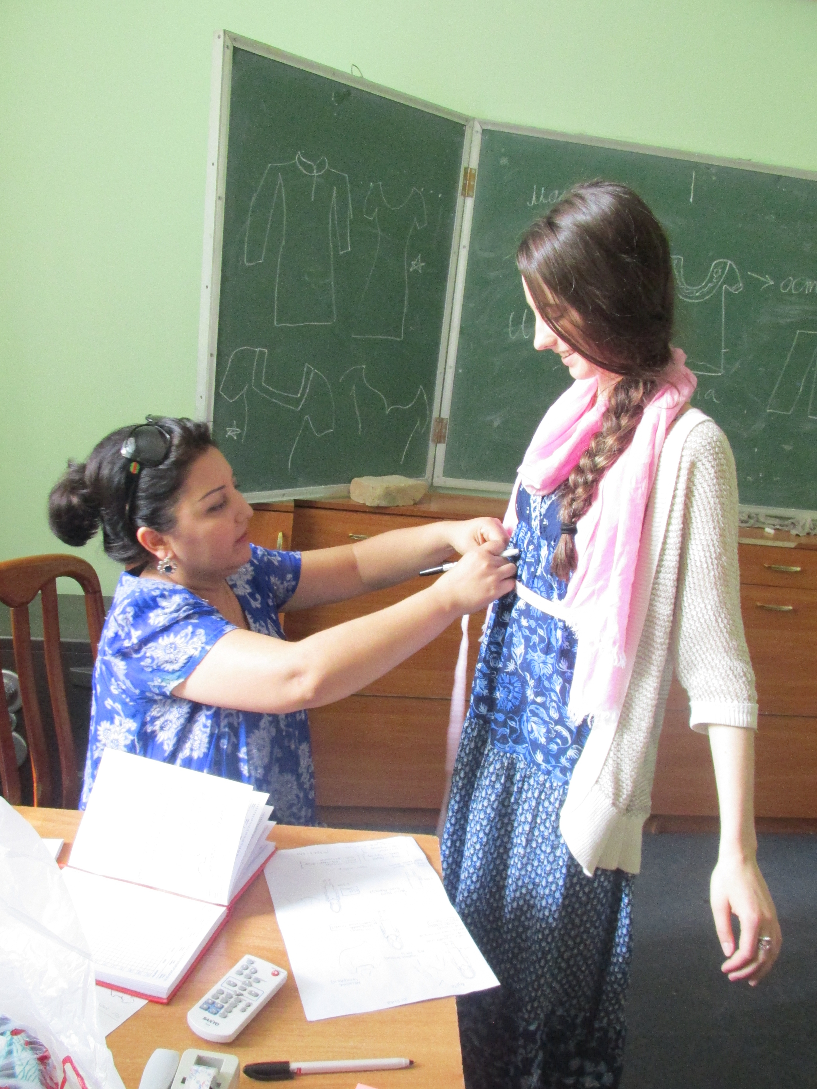 Nayala get measured by the дyзанда (seamstress) for my кyрта (women's Tajik national dress).