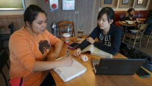 Nsli-y student receiving help from a Korean College student with her work.
