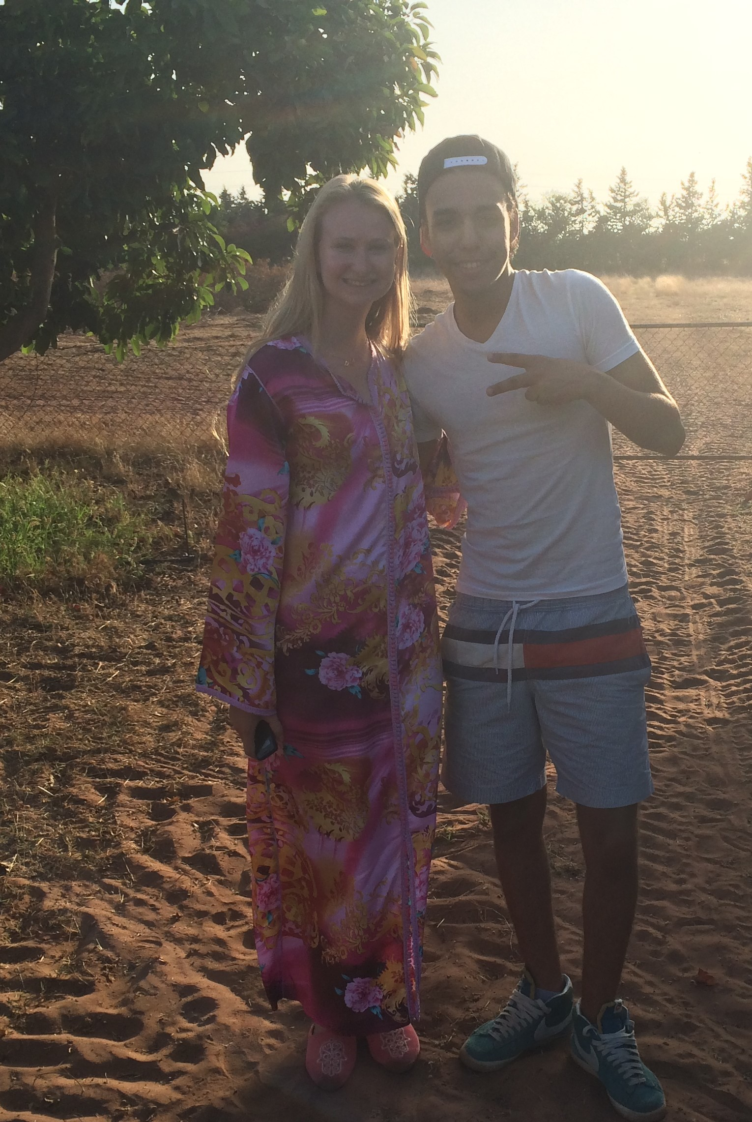 Anna Rose, wearing a pink dress, and her host sibling, in casual dress, on a sandy terrain.