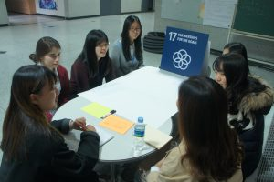 Students discuss around a table.