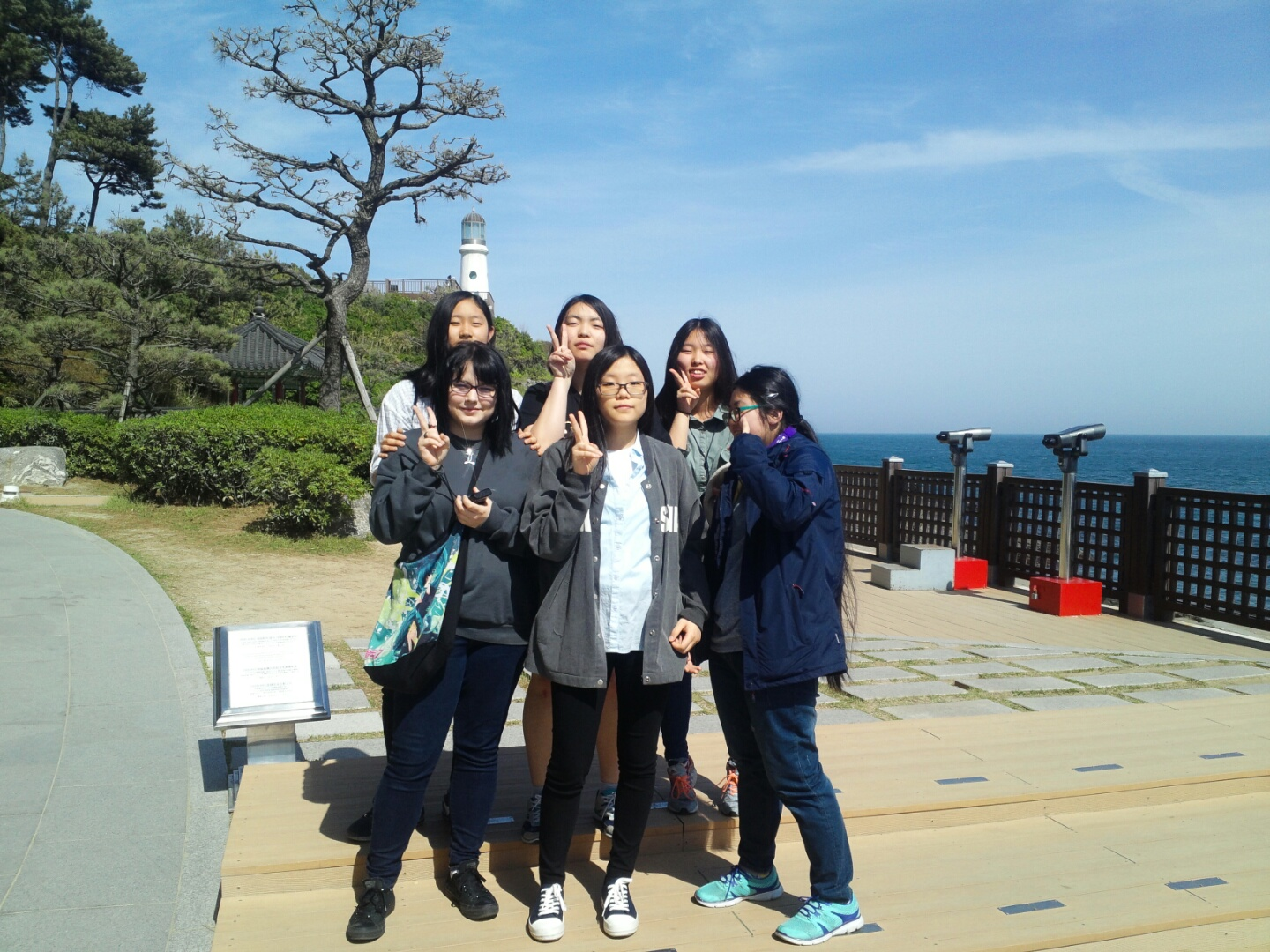 NSLI-Y student poses with her Korean classmates in front of a lighthouse, with the ocean to their left.