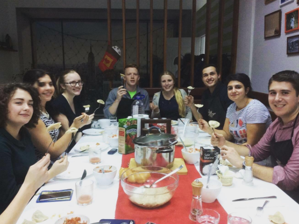 NSLI-Y students eating dinner together after a culinary master class led in Russian. The local coordinator taught students how to make traditional Moldovan and Russian dishes, such as pelmeni (пельмени), which is a meat filled dumpling, and borscht (борщ), which is a traditional Russian beet soup.