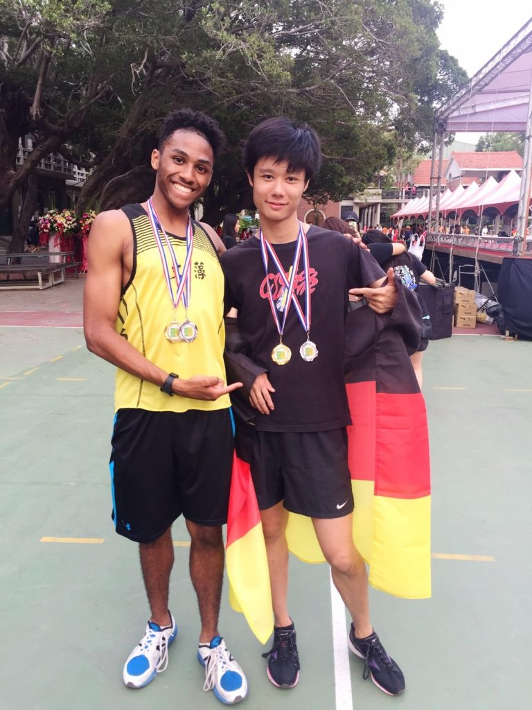 Joey and his friend posing with their track medals around their neck.