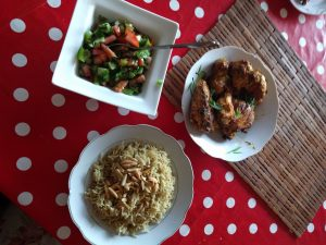 Meenu's host mother prepared a meal of rice, chicken, and salad laid on the table.