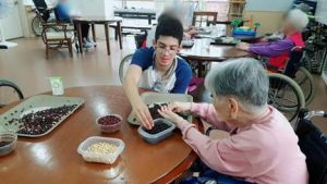 NSLI-Y Korean participant Fernando helps an elderly person separate beans into the appropriate buckets to practice motor skills.
