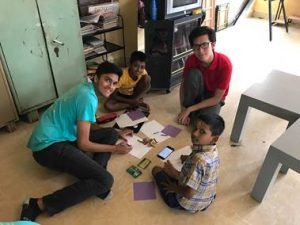 NSLI-Y Hindi participants Varun and Zach draw and play with schoolchildren from orphanage for their community service.
