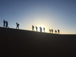 Picture of people walking on a sand dune during sunset